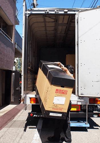 ドライバーの方が自転車の入った輪行箱をトラックに積み込んでいる写真