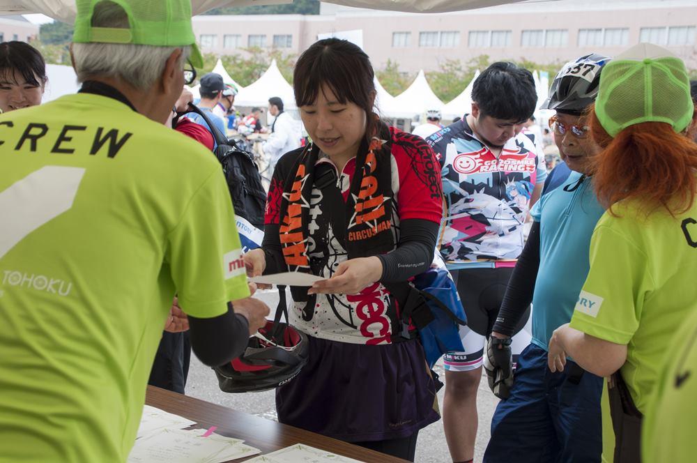 写真:会場の受付でライダーの参加受付手続きの対応を行うクルー