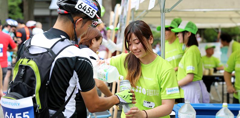 写真:参加ライダーに飲み物を提供するクルー