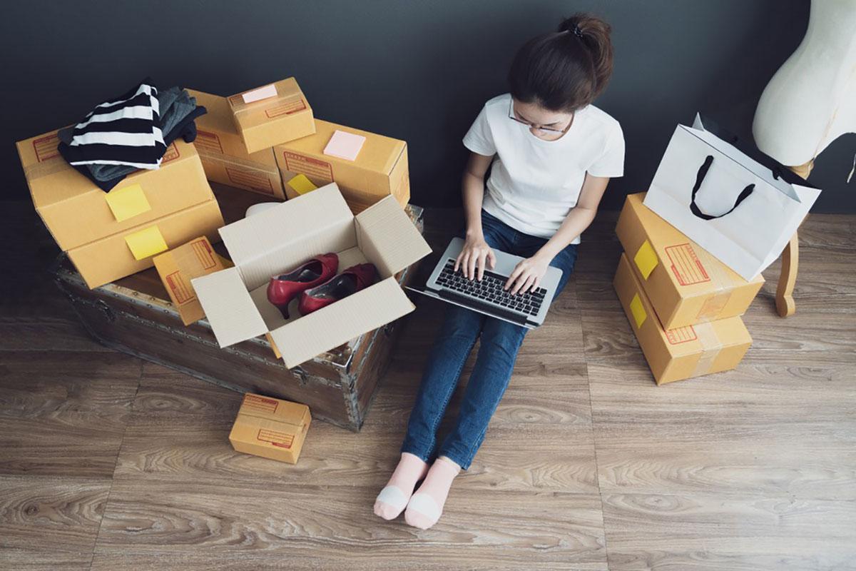 パソコンで不用品を売る女性の画像