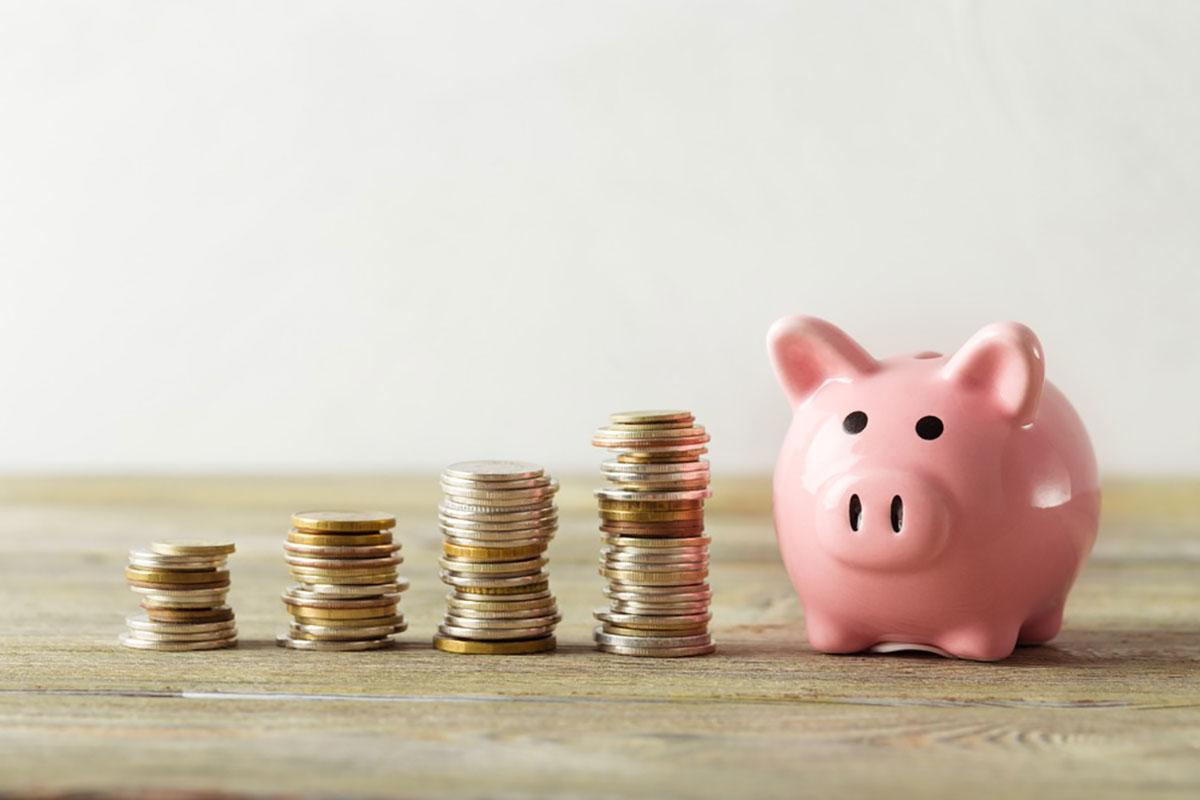 豚の貯金箱の横に硬貨が積み上げられた画像