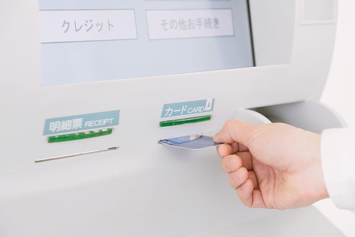 ATMでカードを入れる男性の手の写真