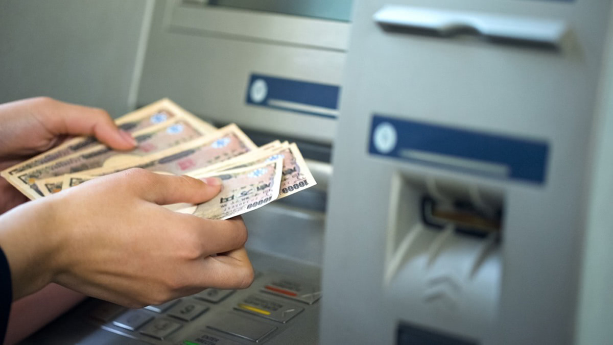 ATMでお金を引き出す手元の画像