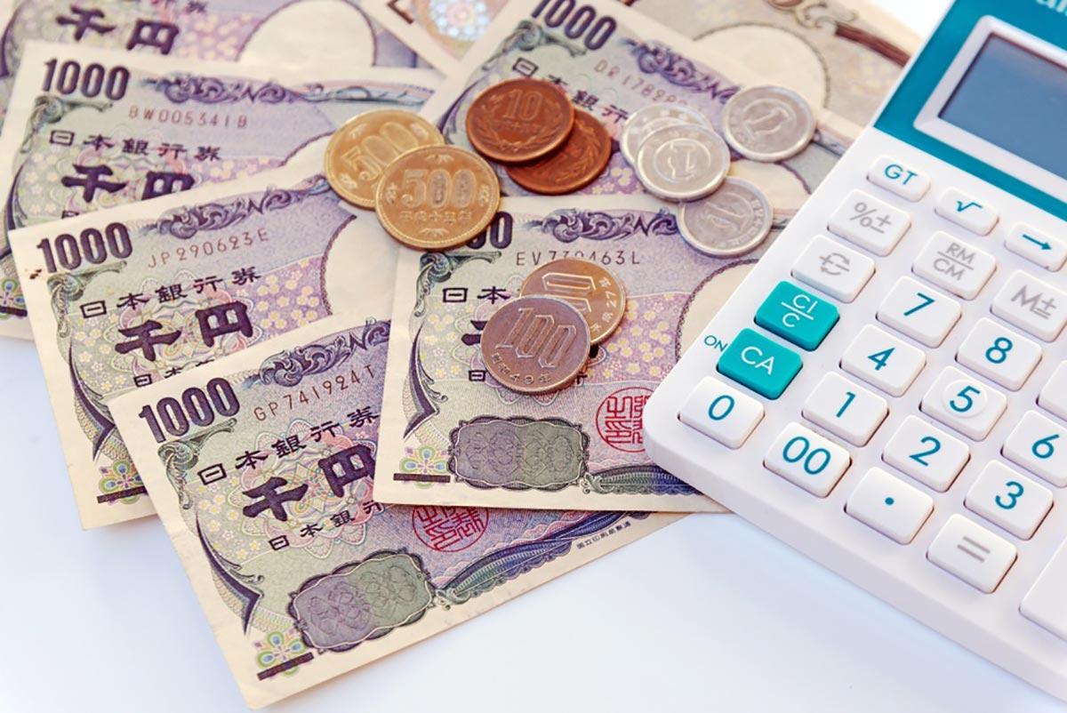 電卓とお金の画像