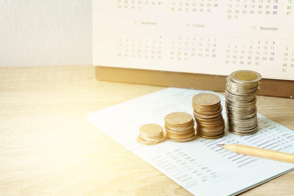 種類ごとに積まれているコインと、カレンダーと鉛筆が写った画像