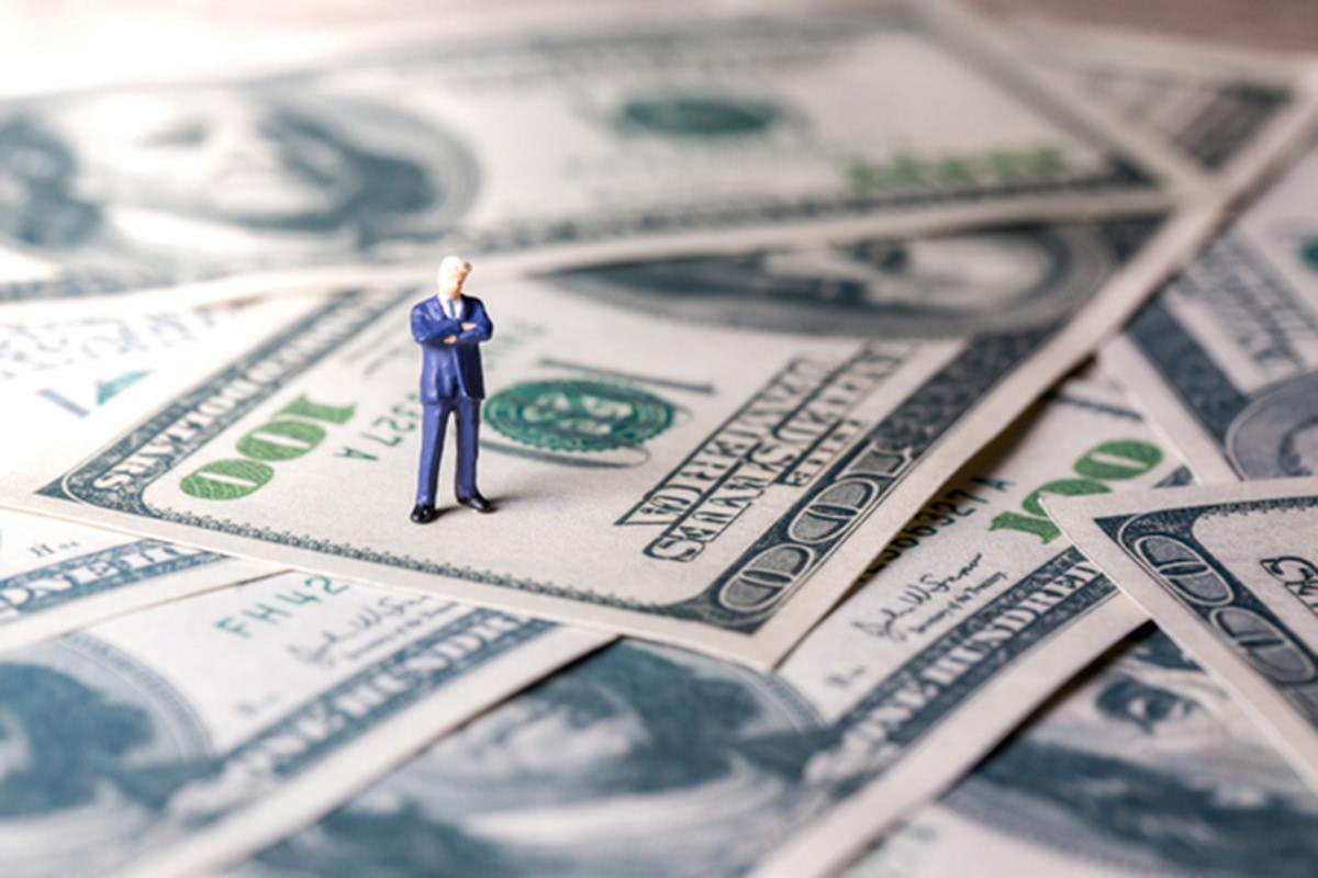 紙幣の上に男性のミニチュアが置かれている画像