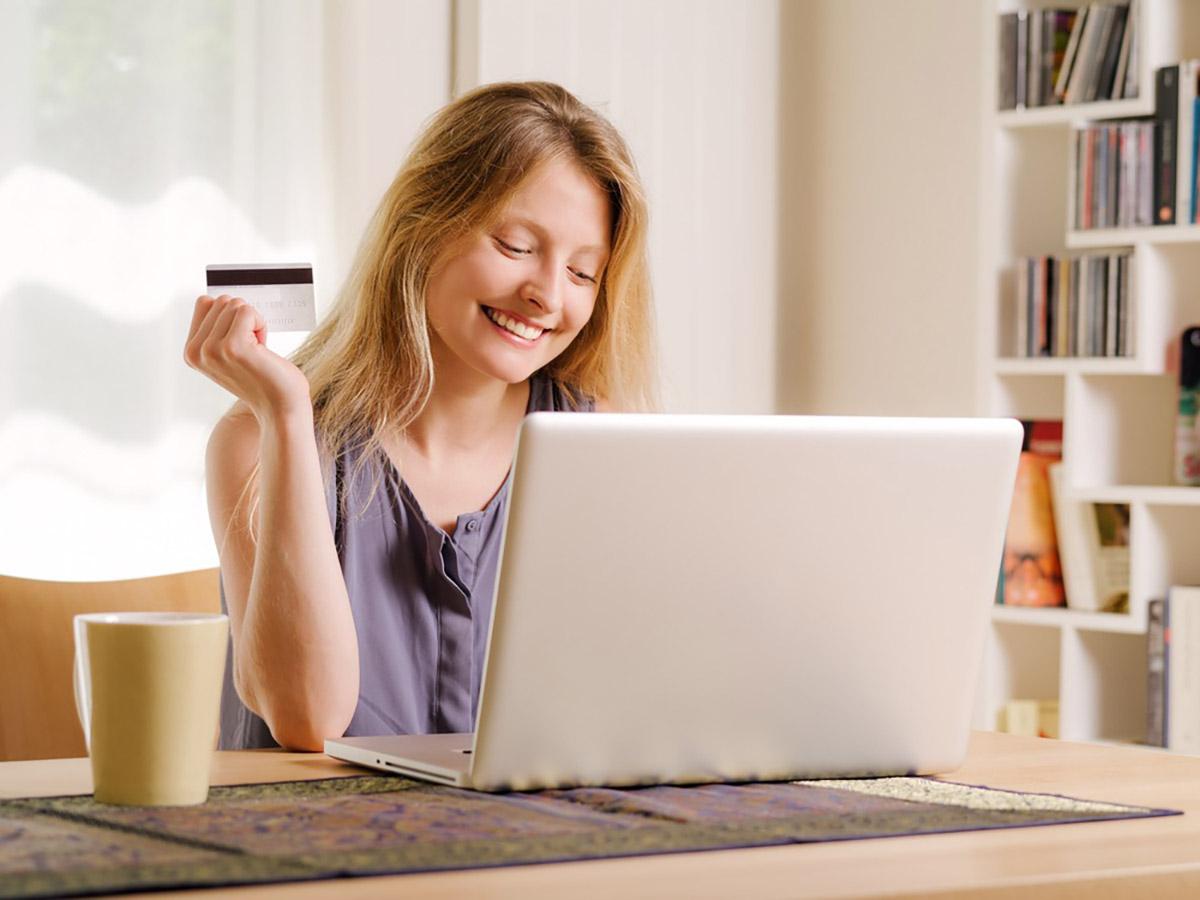 片手にカードを持ってほほえみながらパソコンに向かう女性の画像