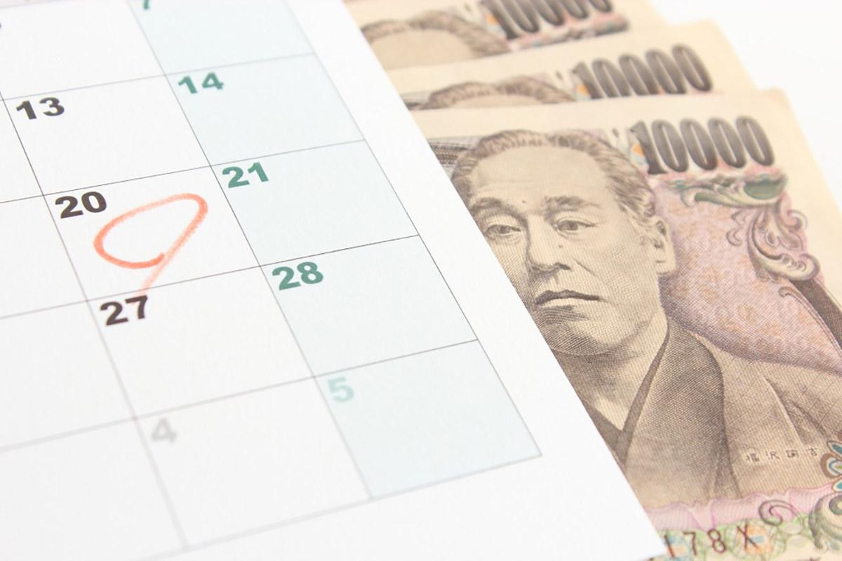 一万円札の上にカレンダーが置かれ、20日に丸がつけられている画像