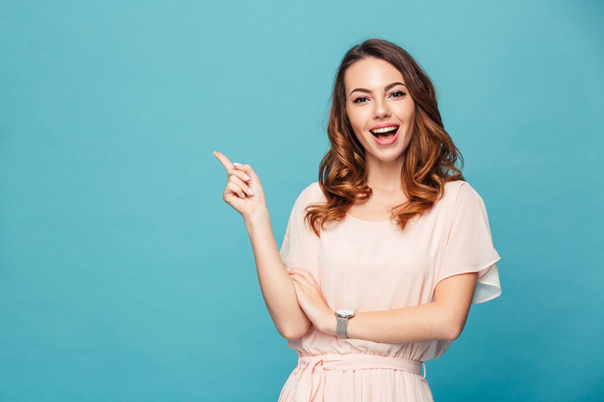 片手で上方向を指さしながら笑う女性の画像