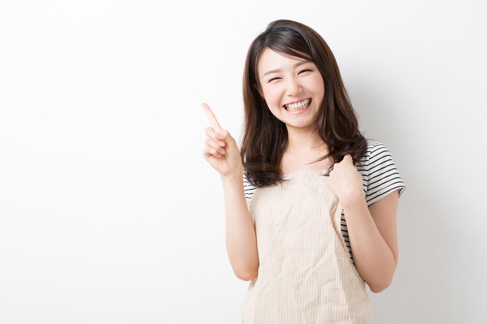 笑顔で人差し指を立てている女性