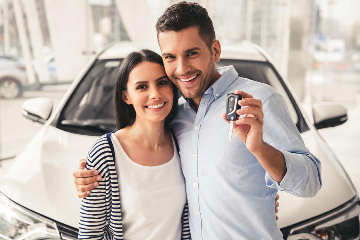 車の前で鍵をもって笑うカップル