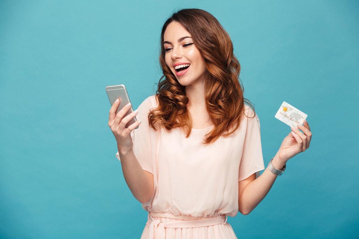 クレジットカードと携帯電話をもつ女性