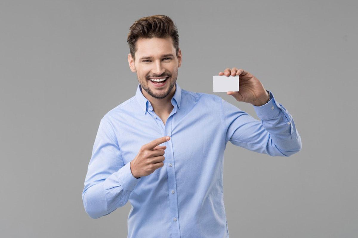 クレジットカードを持って指さす男性