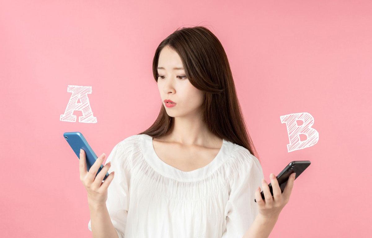 両手に携帯を持つ女性