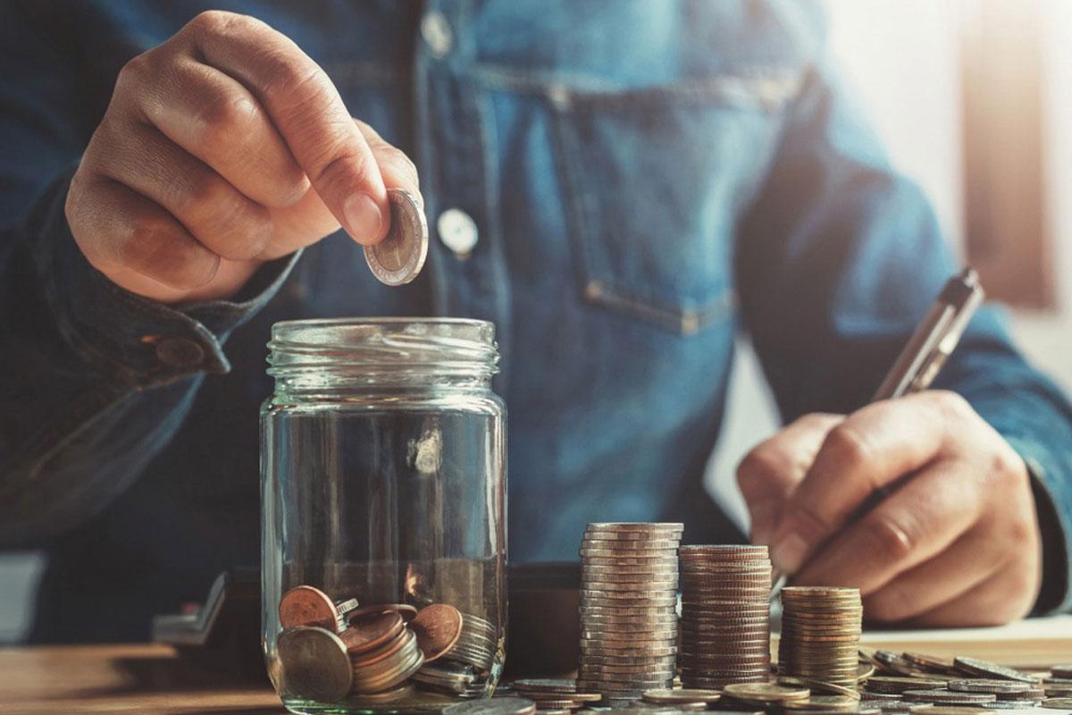 透明な瓶にコインをいれている男性