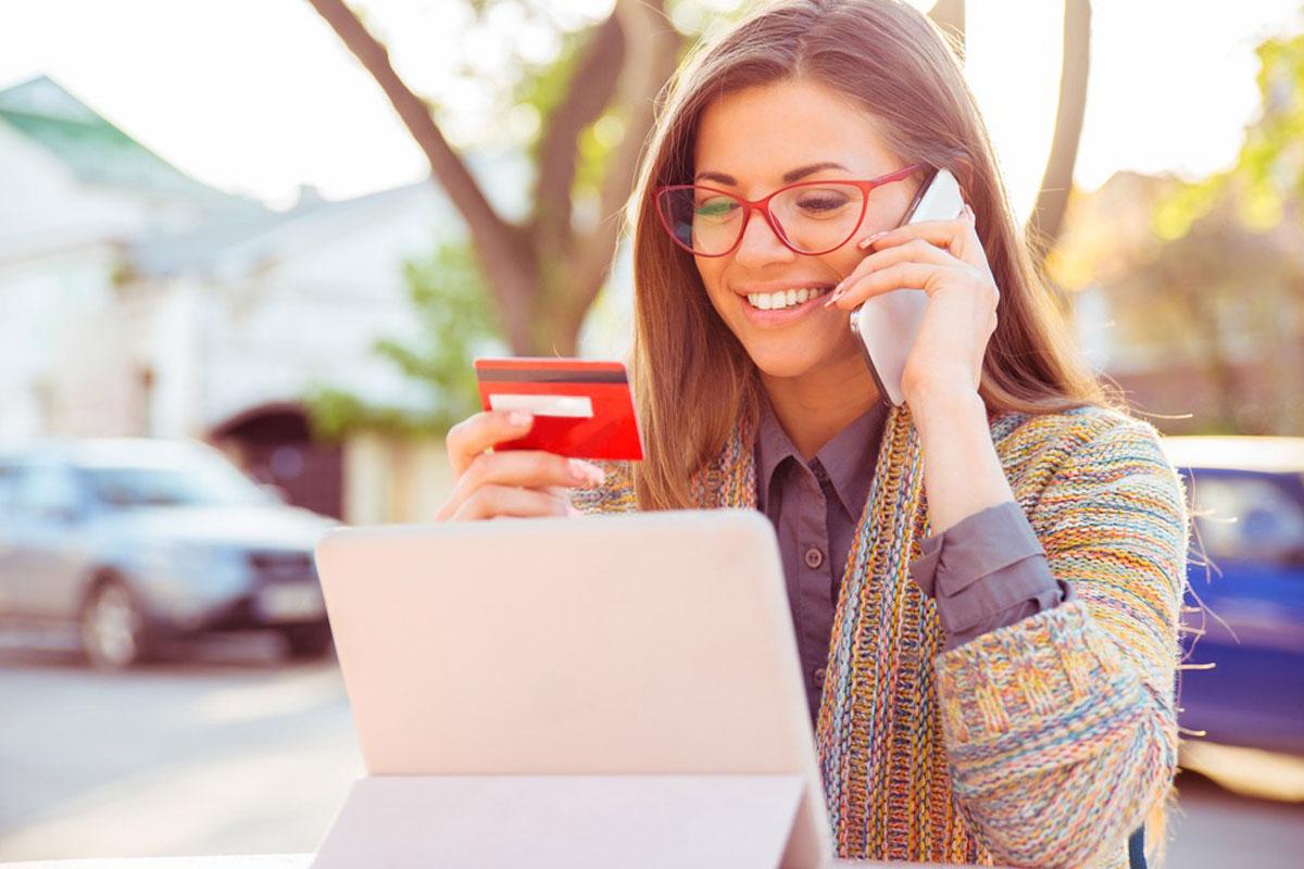 手に持っているカードを見ながら笑顔で電話をする女性