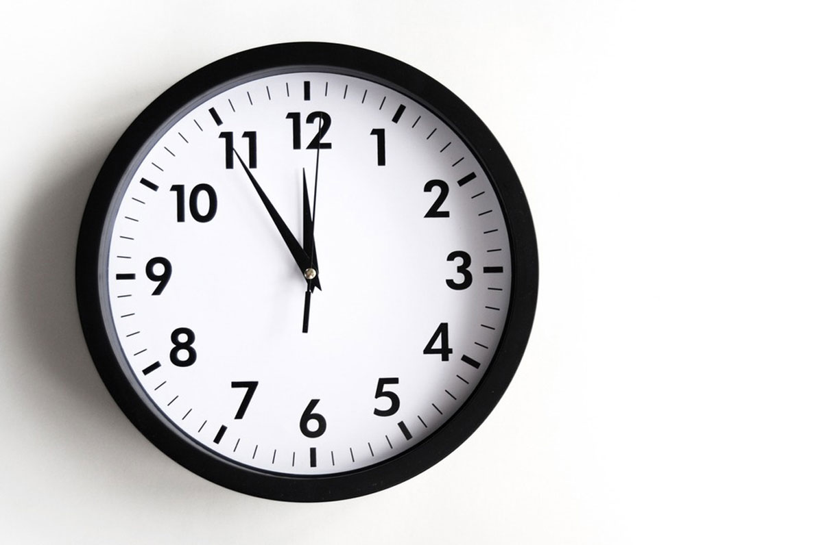 11時55分を指す丸いアナログ時計