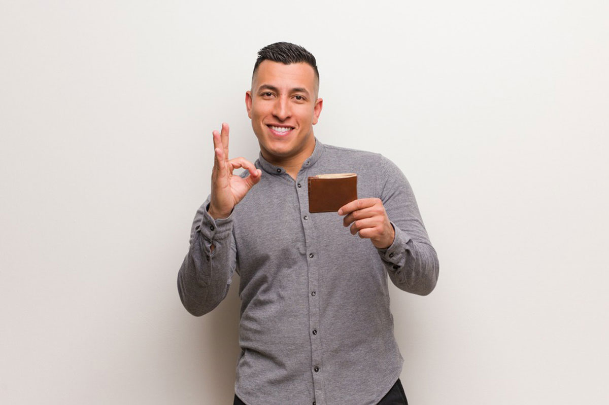 財布をもって手でOKサインをつくる若い男性