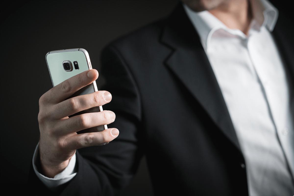 男性がスマートフォンを片手に持っている画像