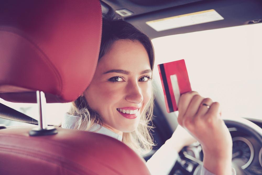 カードを持って車の後部座席を振り返る女性の写真