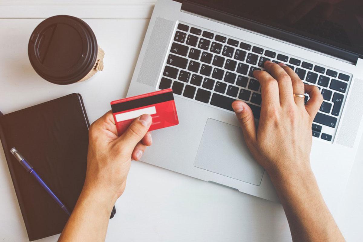 クレジットカードを片手に持ちながらパソコンを操作する手元の画像