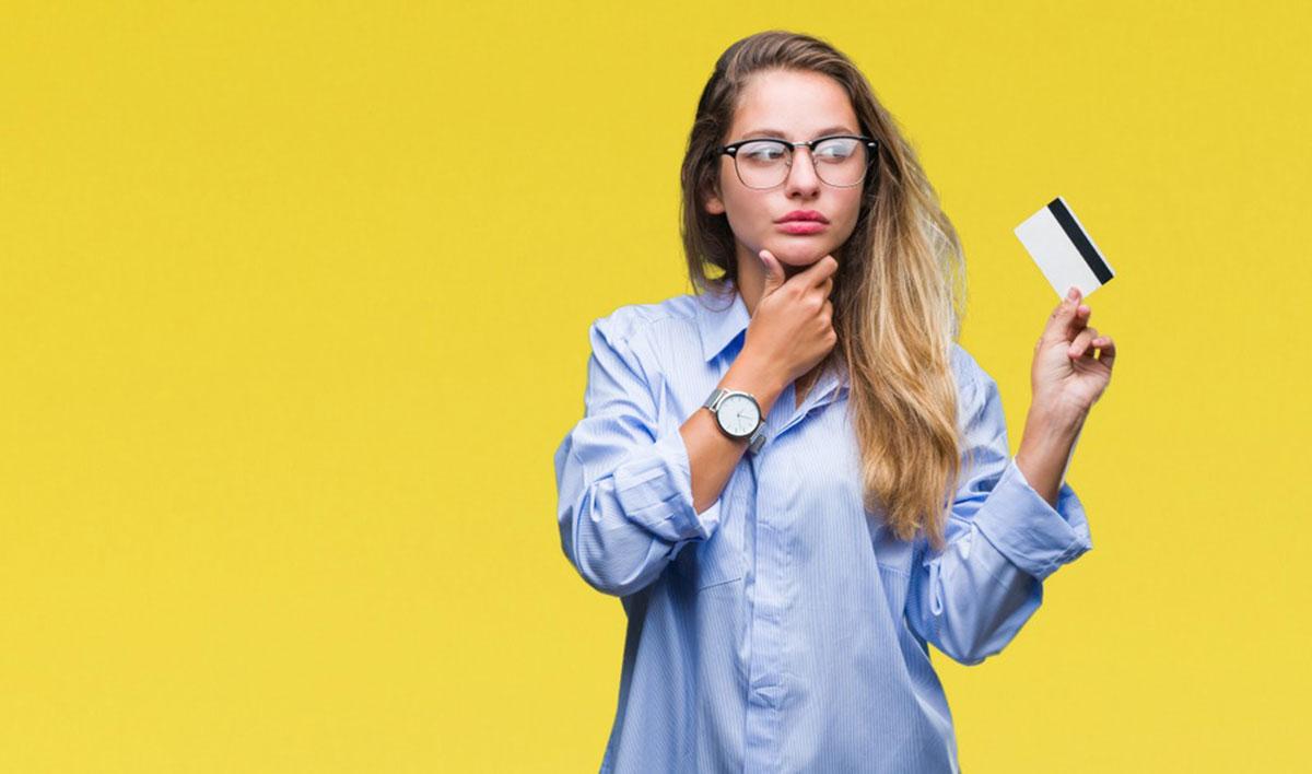 クレジットカードを片手に持ちながら考え事をしている女性の画像