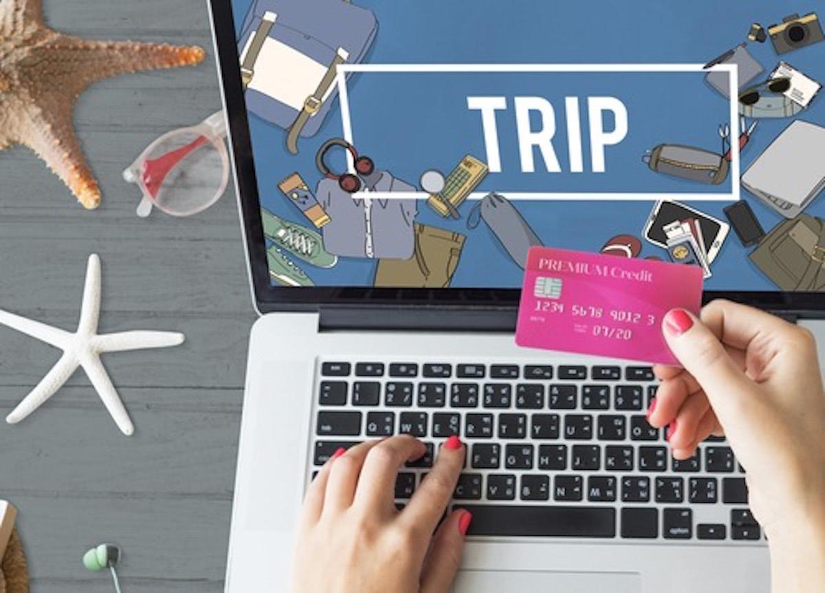 TRIPと書かれたパソコンとクレジットカードを片手に持っている画像