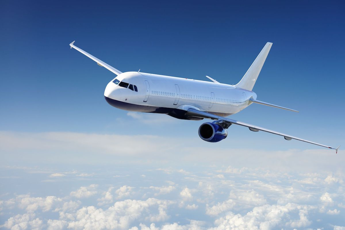空を飛ぶ飛行機の画像