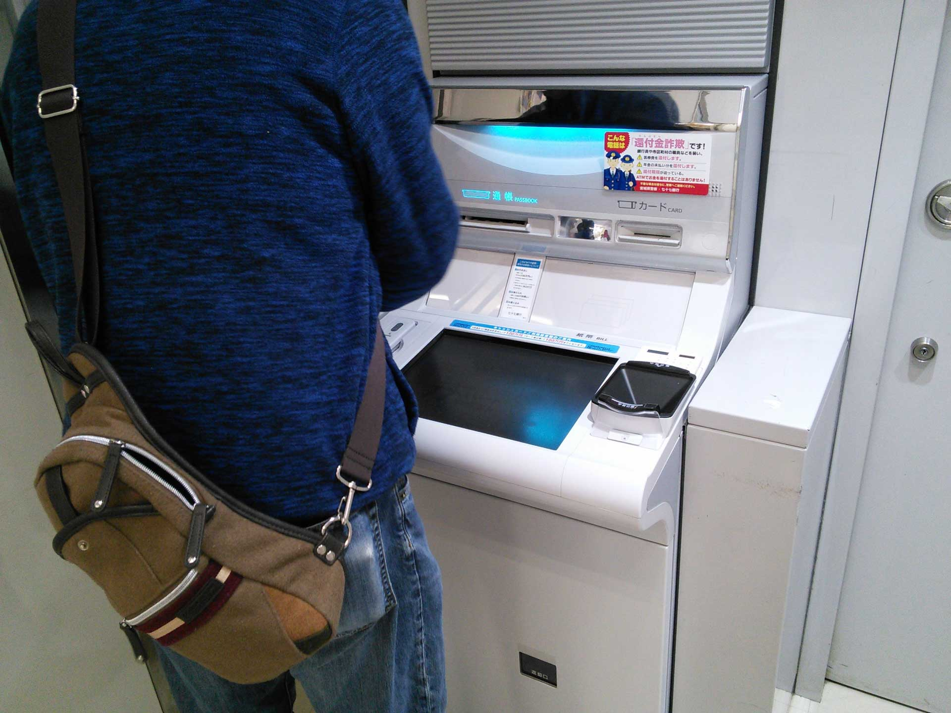ATMを操作する後ろ姿の画像