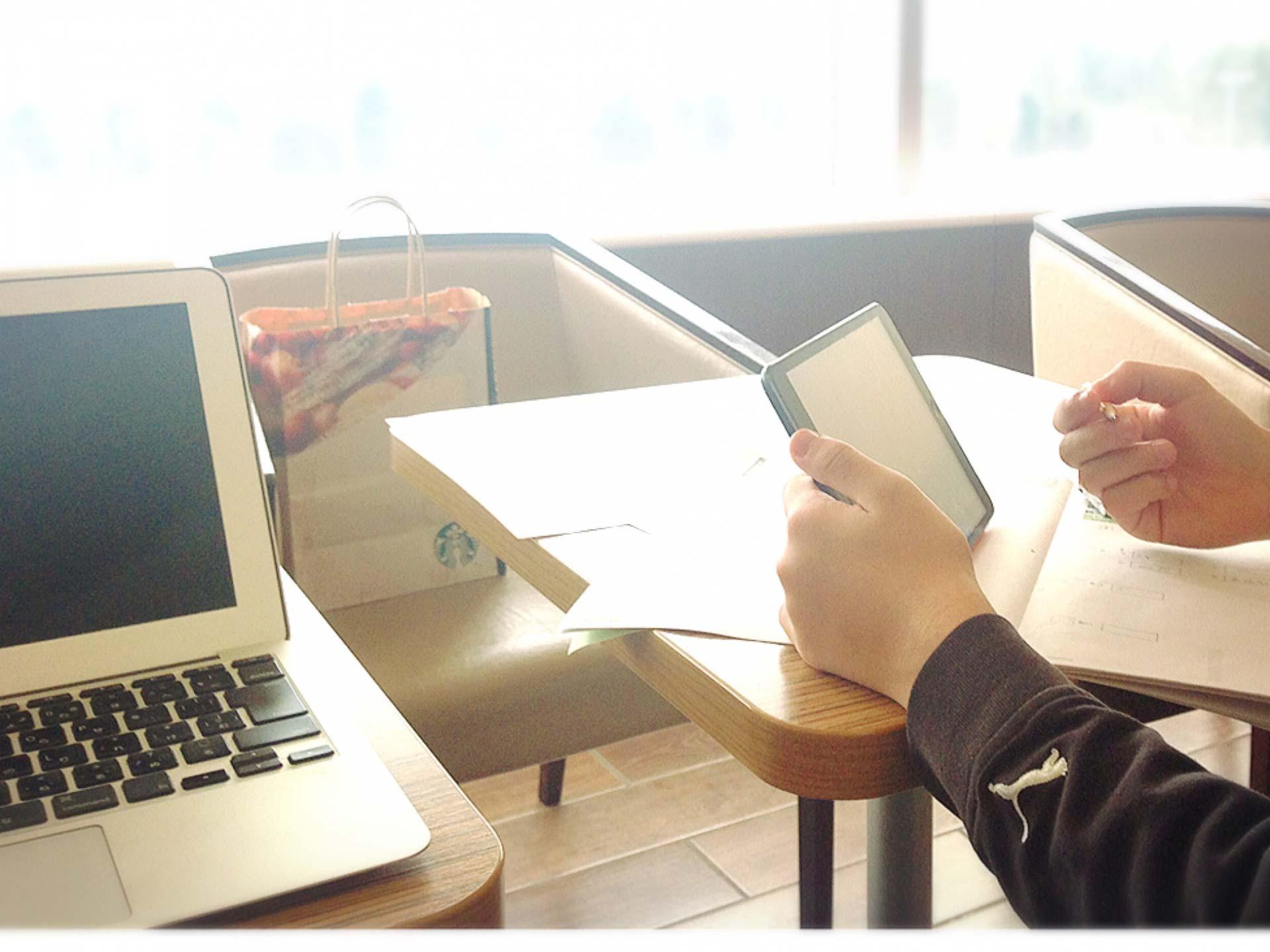 タブレットを見ながらノートに筆記する手元の画像