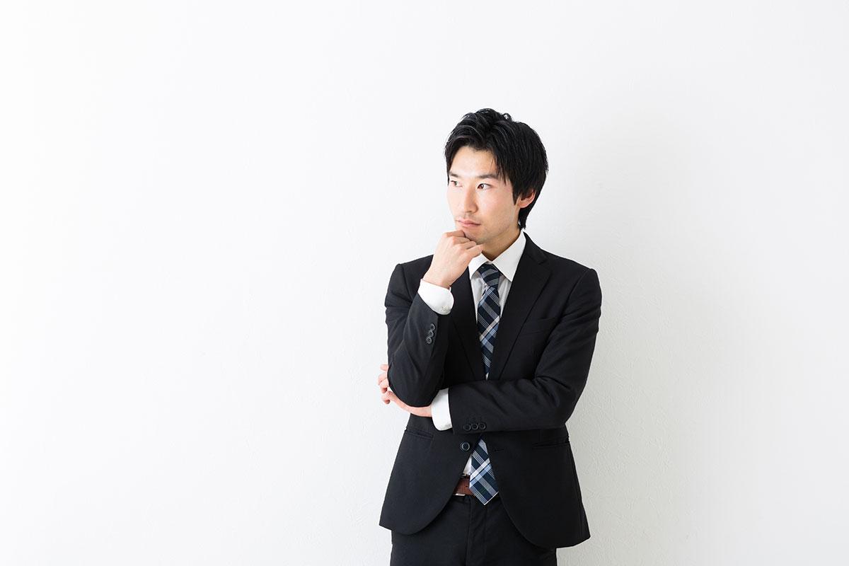 スーツを着た男性が悩んでいる画像