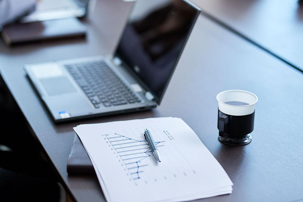 ノートパソコンと資料が机に置かれている画像