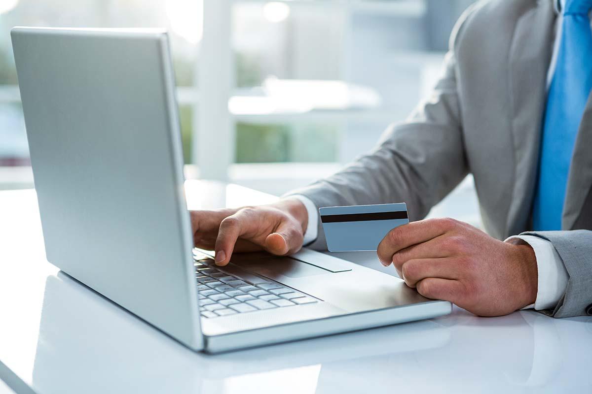 クレジットカードを片手に持ちパソコンを操作する男性の画像