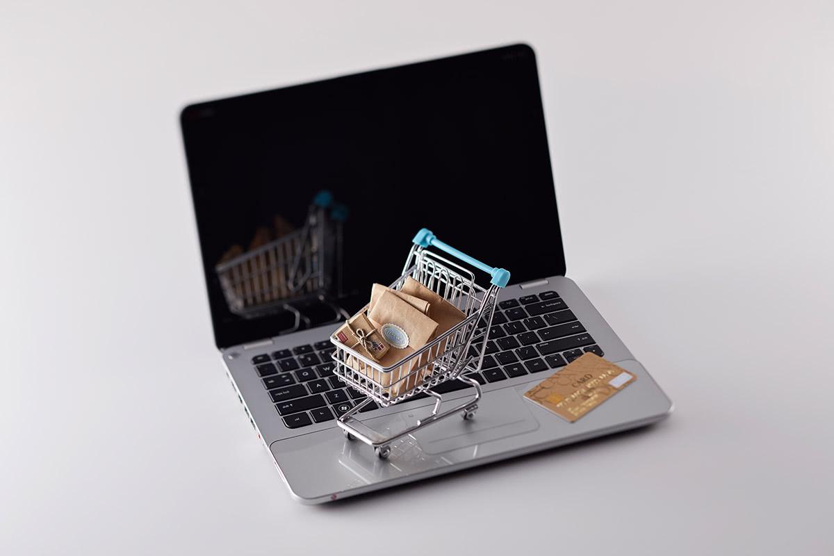 ノートパソコンの上にショッピングカートの模型とゴールドカードが乗っている画像