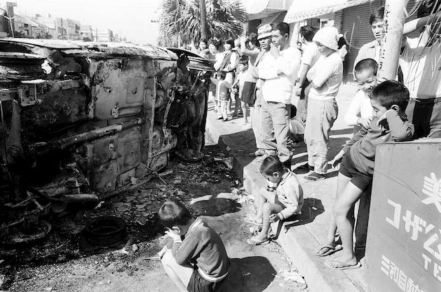 焼けただれた米軍車両とコザ の人々