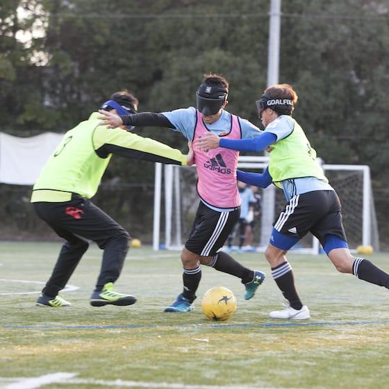 ドリブル突破を狙うブラインドサッカーの選手