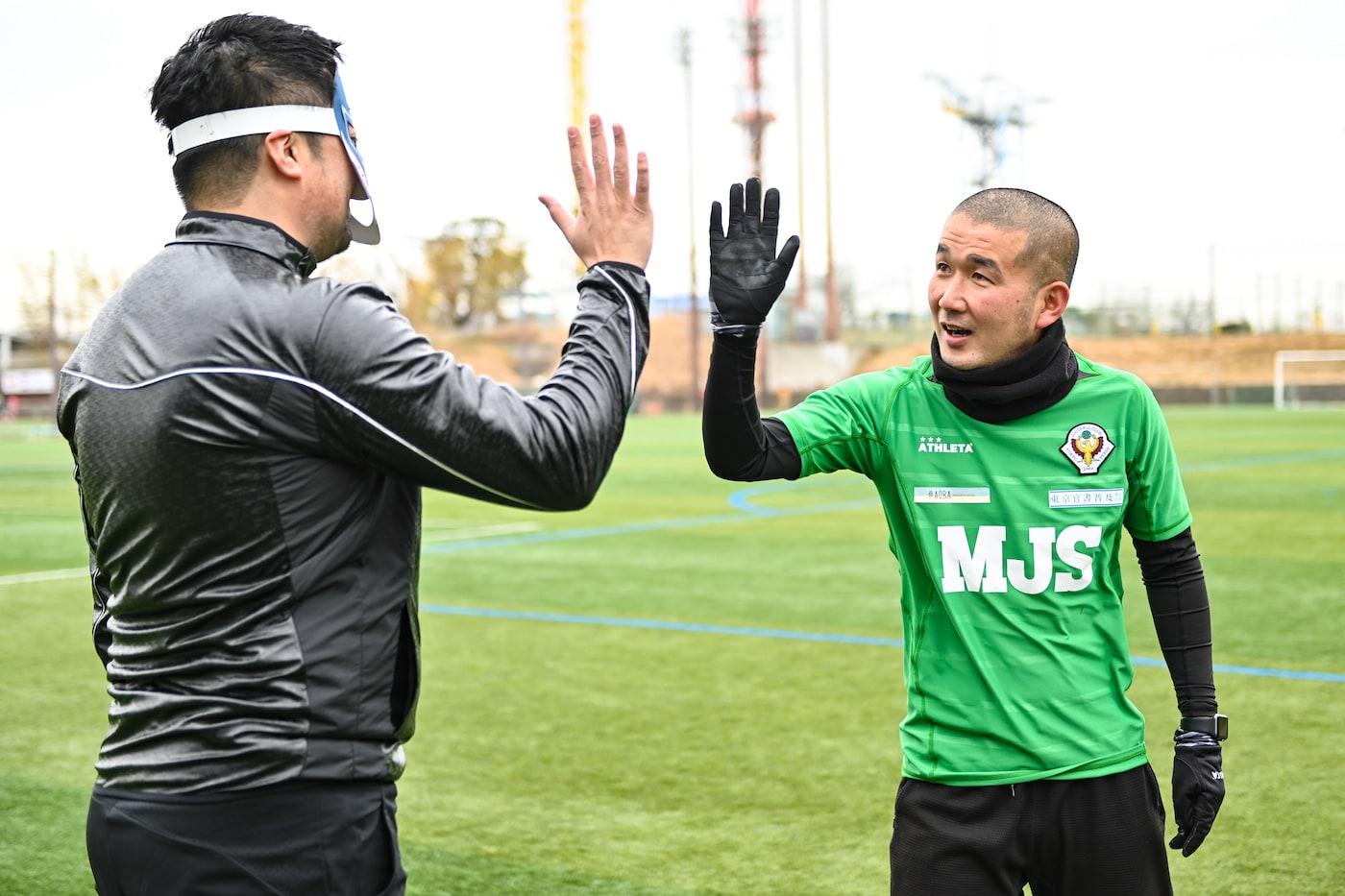 DOマンとハイタッチする中村コーチ