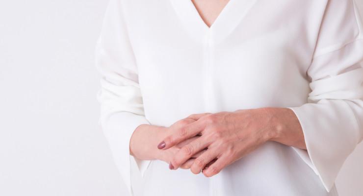 体の前で両手を重ね合わせた女性