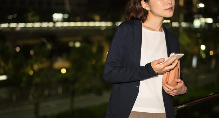 スマホを持って夜の街を歩く女性