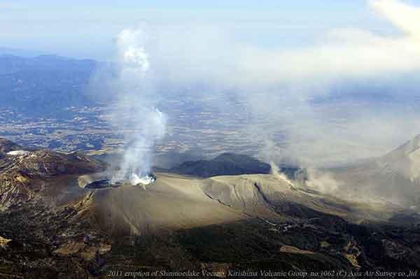 西方向から撮影。火口内の溶岩湖のようすと火口近傍の風下に厚く堆積した火山灰の分布状況がわかる。(2011年2月1日撮影)