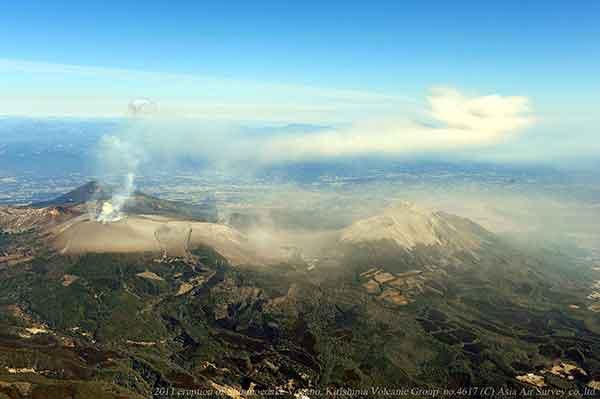 南西方向(霧島市上空)から撮影。新燃岳からの降灰によって中岳、御鉢は白くそまっている。撮影時には視界が開けて御鉢、高千穂峰にかけて火山灰が多量に堆積しているようすがみえる。(2011年2月1日撮影)