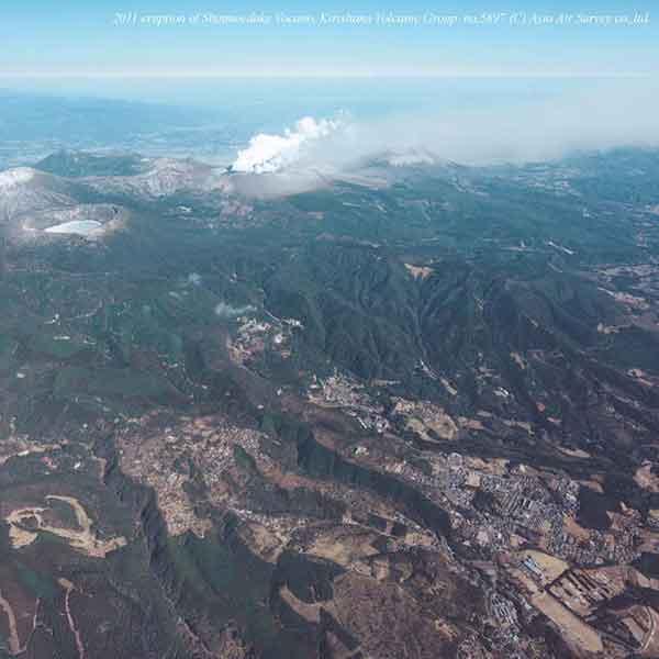 北西方向から撮影。手前右の宅地は霧島温泉地区。温泉地区から奥の噴火中の新燃岳火口が近くにみえる。(2011年1月31日撮影)