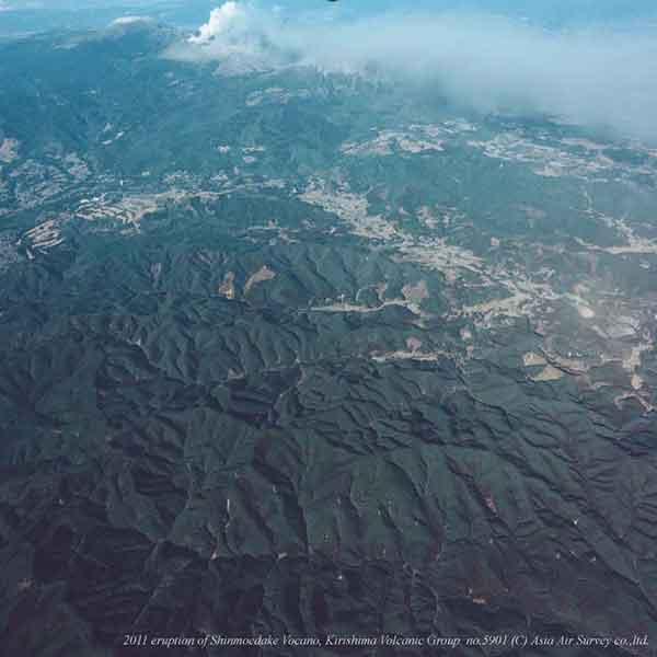 南西方向より撮影。写真奥の新燃岳火口から写真右上(南東)都城市方面へと火山灰が帯状に流されていくようすがみえる。(2011年1月31日撮影)