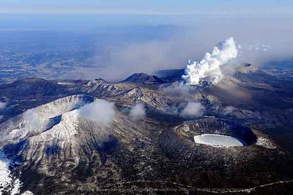 北西(えびの市)方向から撮影。手前左は冠雪の韓国岳、手前右は大浪池。新燃岳から南東方向へ広く火山灰が飛散している。(2011年1月31日撮影)