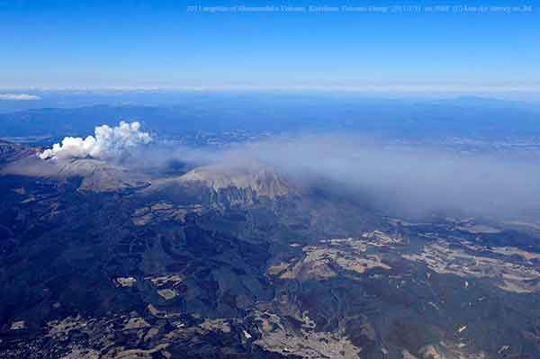 南側から撮影。火山灰は新燃岳から高千穂峰を通り、南東方向の都城市街へ多く降り注いでいるようすが、地表部の植生の色の違いからうかがえる。写真左下の植生が緑色をしているのに対し、写真右下の火山灰雲の下は茶色く変色している。(2011年1月31日撮影)