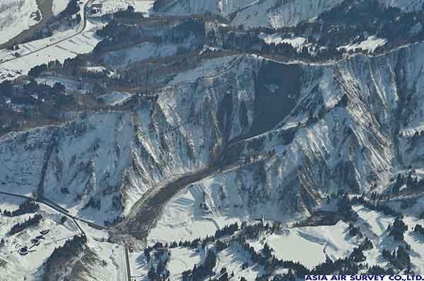 新潟県津南町辰ノ口地区西方斜面。稜線付近から比較的大きな崩壊が発生した。流下した雪混じりの土砂は雪堤を作りながら500m程度流下し、家屋に迫っている。(2011年3月12日撮影)