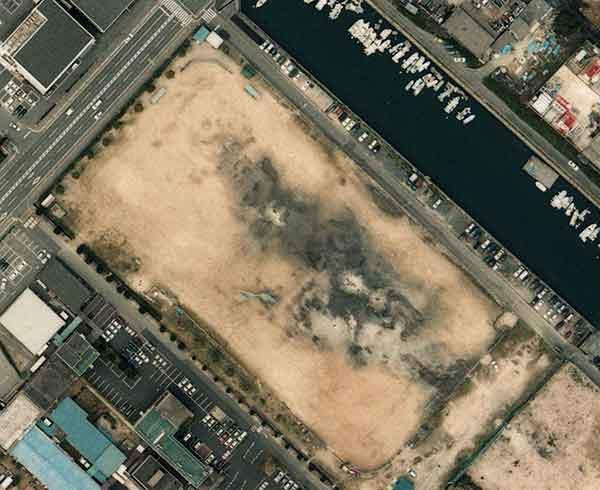 野球グラウンドで発生した液状化現象:黒っぽい部分はまだ湿っている部分。吹き上げられた砂が円形のマウンドを形成した。マウンドの中央部には円形の火口状の地形が確認できる。(2001年3月27日撮影)