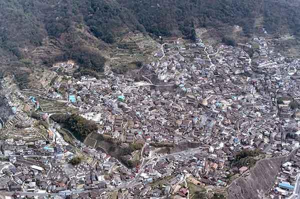 呉市の被害状況:呉市では、屋根瓦やブロック塀、擁壁の崩壊被害が報告されている。この写真では、山地斜面にある住宅の被害状況が、屋根にかけられたブルーシートから推定できる。(2001年3月27日撮影)
