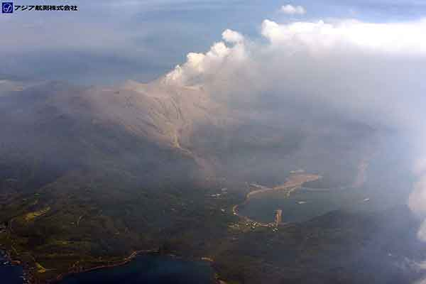 新岳西側斜面全景。写真中央の噴気があがっている場所が新岳山頂(626m)火口。中央下の手前に伸びる桟橋の付け根に位置している集落が本村地区。新岳の西側斜面には、噴火に伴って噴出した火山灰や火砕流堆積物が分布している。本村地区と海を挟んで反対側に位置する防波堤付近には、海水面の変色域が見られる。噴気は、南西方向に延びている。(新岳の北西方向より撮影)(2015年5月29日撮影)