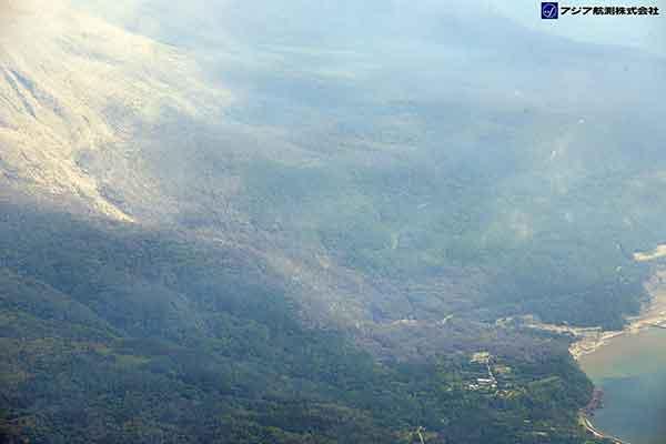 谷の上部に、堆積した火砕流堆積物と倒木が確認できる。谷の出口付近にある建物を見ると、大きな損傷は受けていないように見える。谷に沿って樹木の変色領域が伸びている。(新岳の北方向より撮影)(2015年5月29日撮影)
